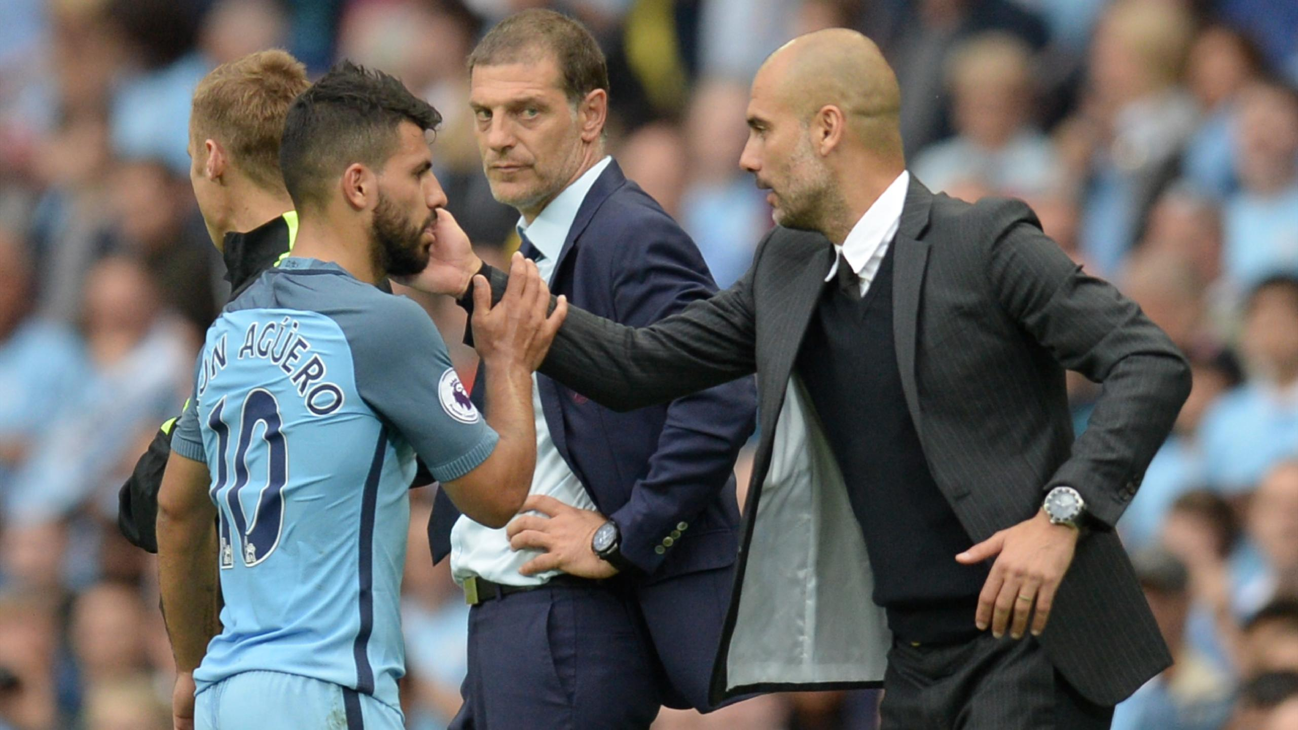 Manchester City's Spanish manager Pep Guardiola (R) greets Manchester City's Argentinian striker Sergio Aguero