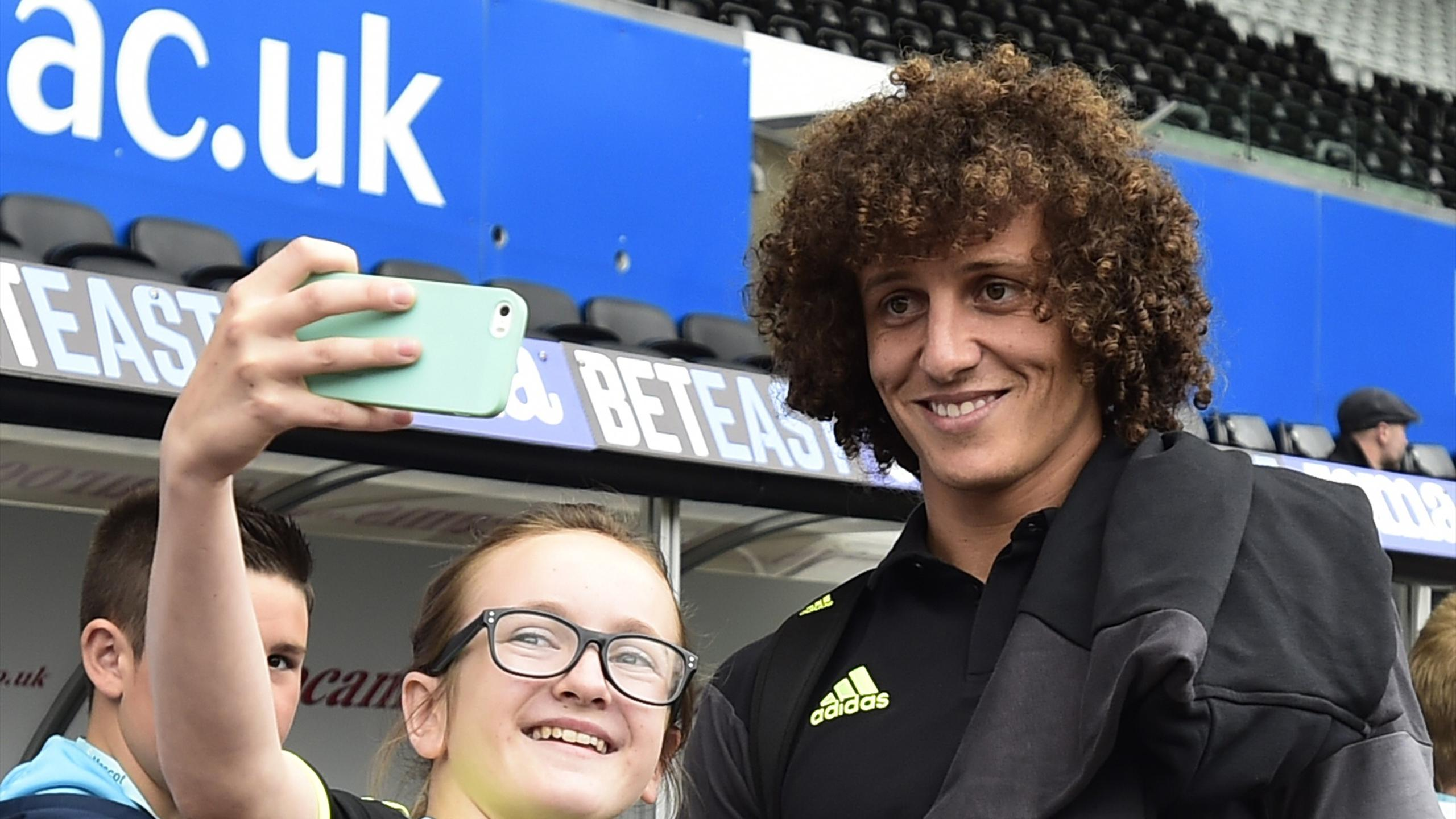 Chelsea's David Luiz poses for a picture with fans before the match