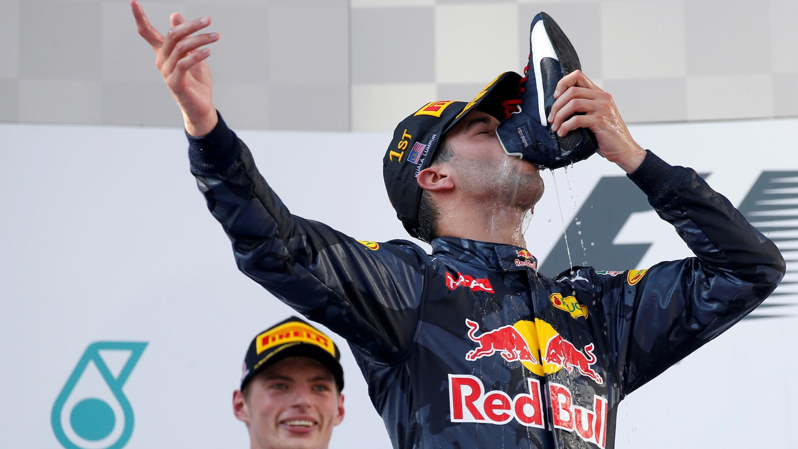 Red Bull's Daniel Ricciardo of Australia drinks from his shoe as he celebrates on the podium in Malaysia