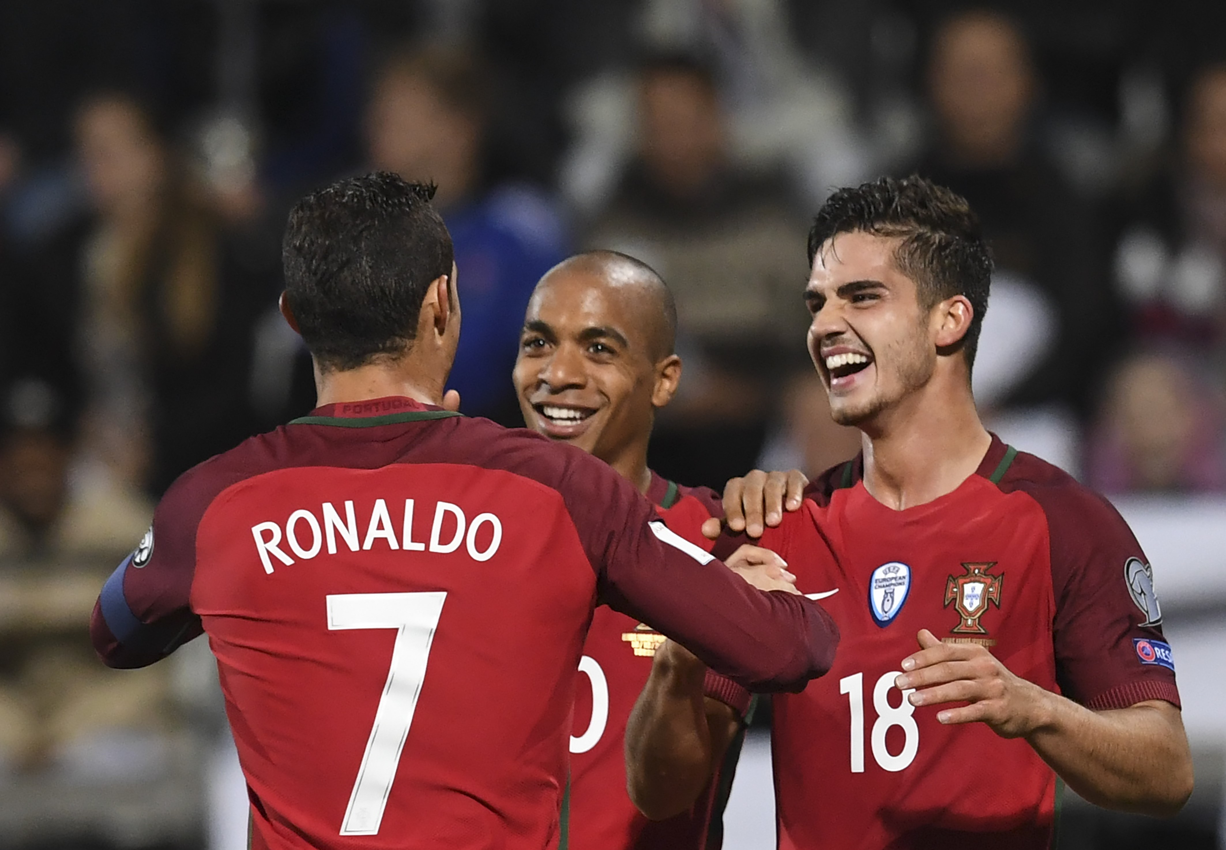 Portugal's forward Andre Silva (R) is cogratulated by teammates midfielder Joao Mario (C) and forward Cristiano Ronaldo after scoring a goal during the WC 2018 football qualification match between Faroe Islands and Portugal in Torshavn on October 10, 2016