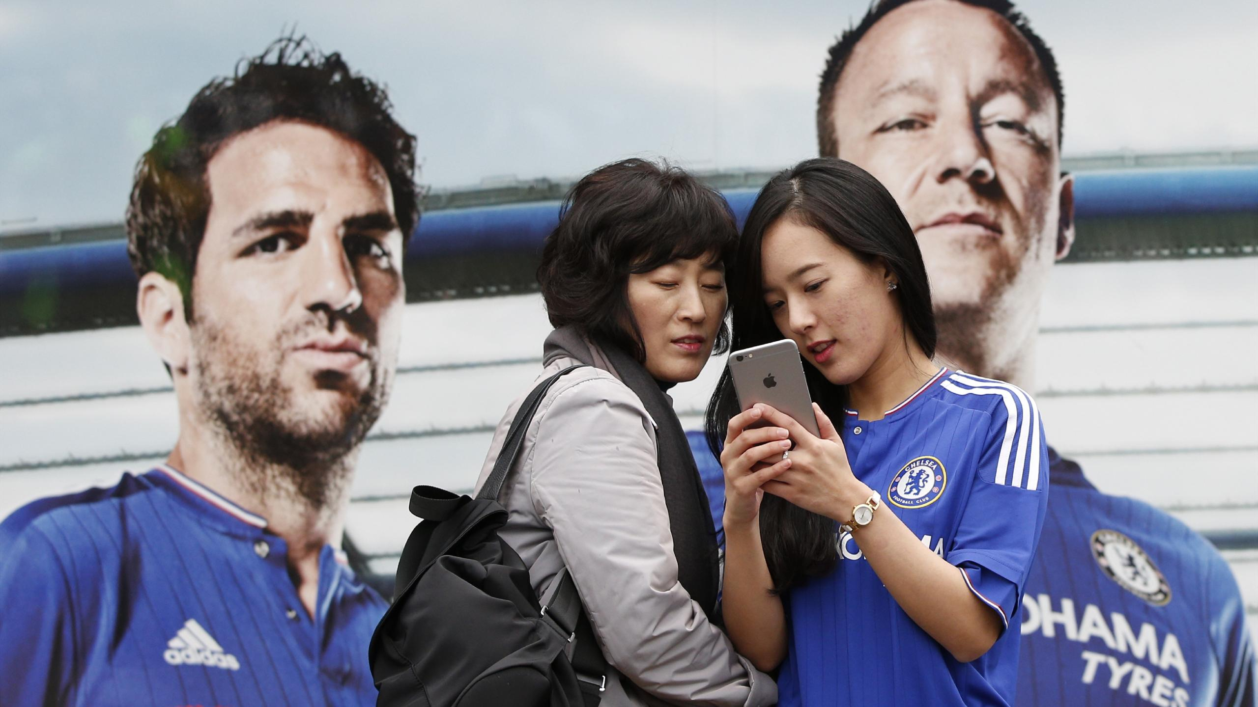 Fans pose by a poster of Chelsea's Spanish midfielder Cesc Fabregas and Chelsea's English defender John Terry