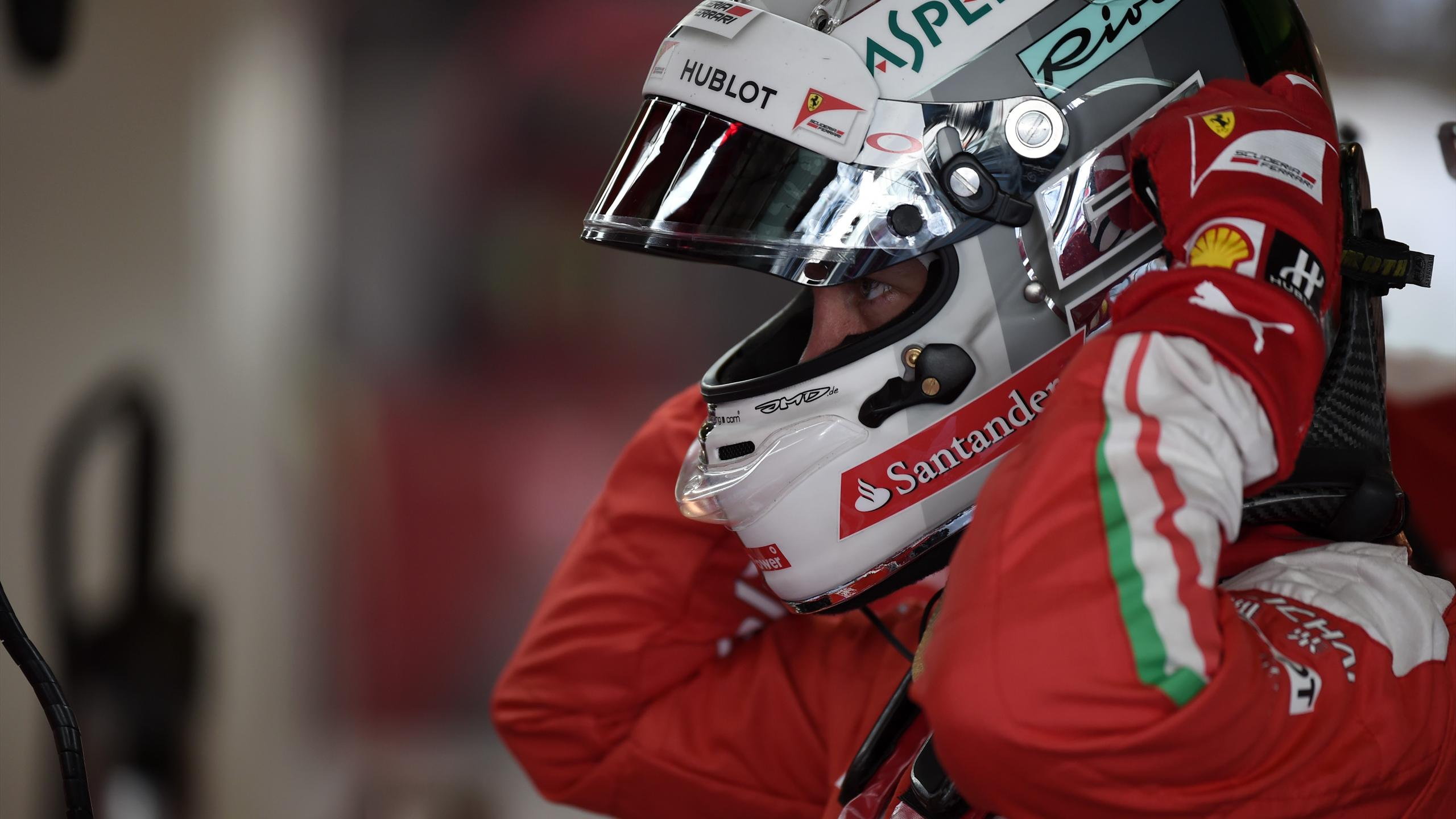 Scuderia Ferrari's German driver Sebastian Vettel stands the pits during the third practice session as part of the Abu Dhabi Formula One Grand Prix