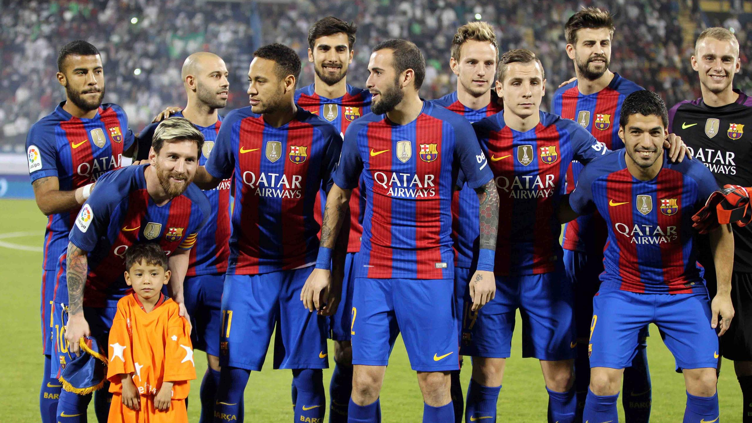Lionel Messi (L) and Barcelona's team pose for photographs with six-year-old Afghan boy Murtaza Ahmadi before the match