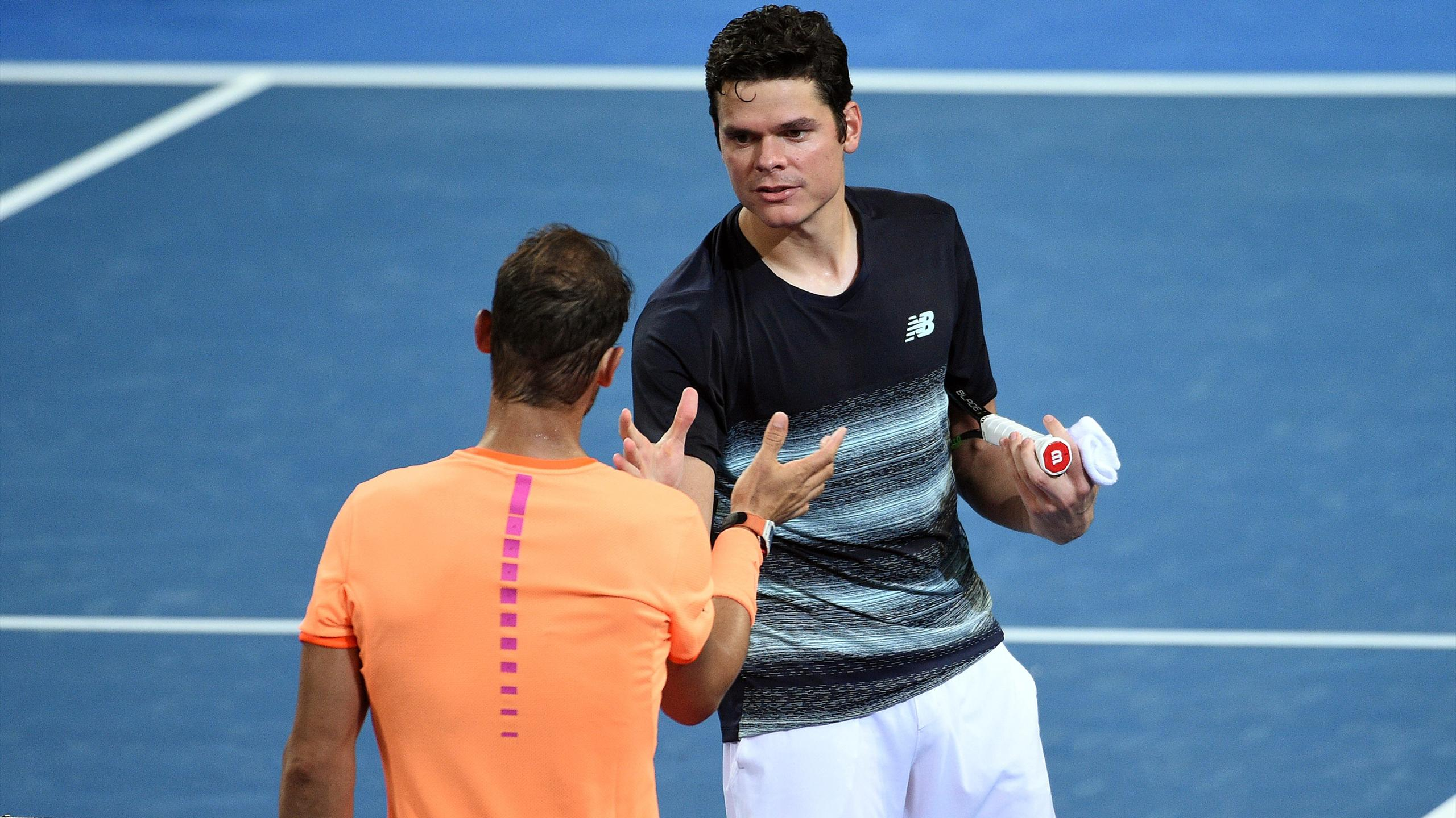 Milos Raonic shakes hands with Rafael Nadal after their match in Brisbane